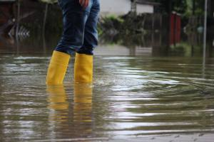 person in rain boots walking in flooded area